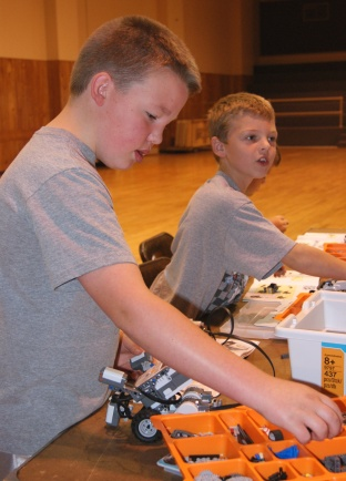Trevor Weitzenkamp of Oakland and Isaac Ruwe of Tekamah sort through hundreds of little Lego pieces to correctly assemble their NXT Mindstorm robot at the UNL Extension sponsored robotics camp held last week in Tekamah. Photo Credit/Mary Loftis, Extension Assistant.
