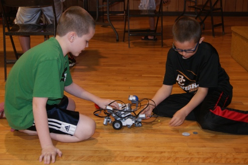 River Wallerstedt and Luke Richards both of Oakland, work together to correctly assemble this NXT robot at the Razzle Dazzle Robotics Camp last week in the Tekamah Auditorium. Photo Credit/Mary Loftis