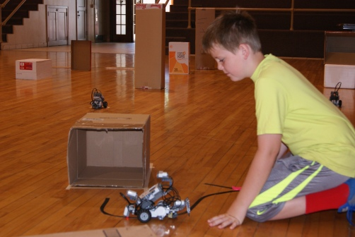 "Miles Pearson of Oakland proudly demonstrated his robot as it follows the black tape line and parks in the ""garage"" just like he programmed it to do during the Razzle Dazzle Robotics Camp last week. The robotics workshop was conducted by UNL Extension Educator, Carroll Welte assisted by summer intern, Nick Bohannon."