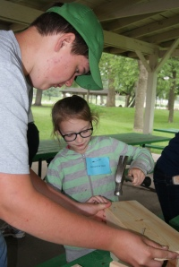 Alex Davis of Tekamah gets help from Jordan Fullner as she makes a bird house at the 4-H Adventure Camp.  Photo Credit/Mary Loftis, Extension Assistant.