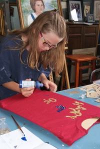 Elise Anderson of Lyons carefully letters her patriotic t-shirt at the 4-H workshop held at Creative Connections in Oakland. Photo Courtesy of Mary Loftis.