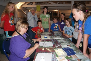 Painter, Connie Buskohl-Barney shares step by step instructions on using a pattern to create the robin in the woods picture while the 4-H members look at examples of the finished product. Taking part in the acrylic painting workshop were: Jayden Fleischman, Mary Tomes,  Connor Davis, Riley Davis, Miranda Bracht, Josie Richards, Alex Davis, and Anna Wakehouse.  Photo Courtesy of Mary Loftis.