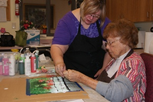 Connie Buskohl-Barney assists Marcella Hennig with her painting stroke as part of the Mneme Therapy demonstration at Oakland Heights last week.  Photo Courtesy of Mary Loftis.