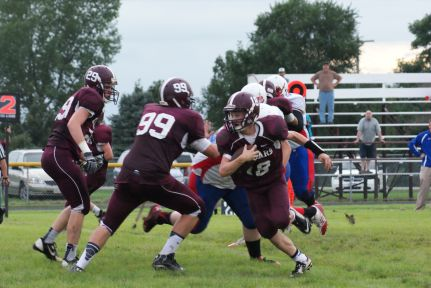 Charles Webb, 29 and Cole Christoffersen, 99, block for ball carrier Montana Riecken. Photo Credit/Pat Sharp LDNE.