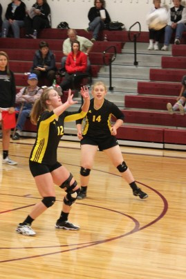Brianne Haskell readies herself for the ball as Abby Peterson is ready to help. Photo Credit/Rhonda Hansen.