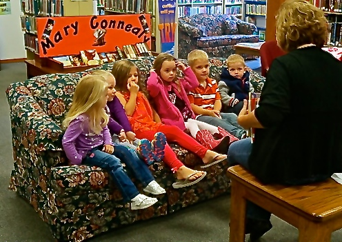 Oakland Public Library Director Rosa Schmidt reads to Ava Johnson, Avery Christensen, Hilary Ray, Laityn Johnson, Paxton Miller and Blaise Hartwell on the first day of Story Time, which will be every Tuesday morning at 10:00 a.m. Photo Credit/Denise Gilliland, Editor and Chief, Kat Country Hub.