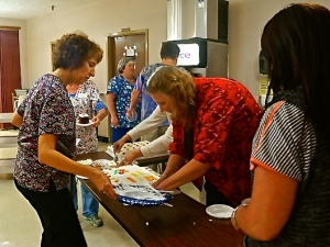 Oakland Heights employees Kim Schwetz, left, Nancy Silvey and Jill Brink busily serve residents cake and other goodies at Cindy's party. Photo Credit/Denise Gilliland, Editor and Chief, Kat Country Hub.
