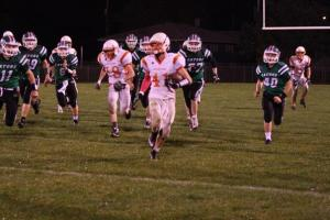 Bryce Uhing runs away from a pack of Wisner-Pilger players, with Tommy Nelson not far behind. Photo Credit/Cheri Droescher.