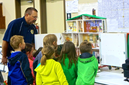 A house displays the many things people should not be doing that can cause fires. Jeff Going, Lyons fire department member and a state fire marshall, quizzes this group of kindergartners on what people should not do. Photo Credit/Denise Gilliland, Editor and Chief, Kat Country Hub.
