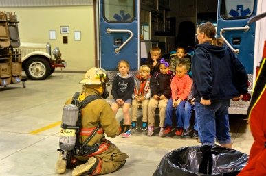 Jesse Raabe, left, a member of the Lyons Fire Department, shows the kids what a fireman looks like in his gear. Angela Whitley, right, describes the gear to them and what it does to protect the fireman. Photo Credit/Denise Gilliland, Editor and Chief, Kat Country Hub.