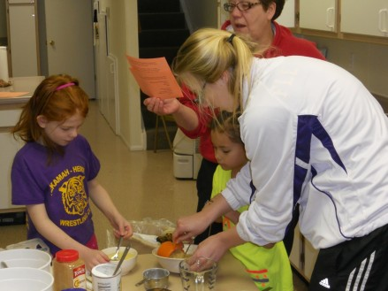 Izzy Connealy and Lily Willing get help making muffins from Jessica Fleischman while 4-H leader, Kim Jackson reads the recipe. The Flying Needs 4-H Club made apple and banana muffins which were shared during Burt County 4-H Week with the residents of the Golden Living Center, the Methodist Church coffee hour and the Extension Office. Photo Credit/Mary Loftis.