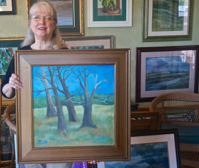 "Jan Cline-Zimmerman, May Artist of the Month, holding her Best of Show Painting ""Last Dance,"" one of the paintings being featured at an open house in honor on Sunday. Photo Credit/Denise Gilliland, Editor and Chief, Kat Country Hub."