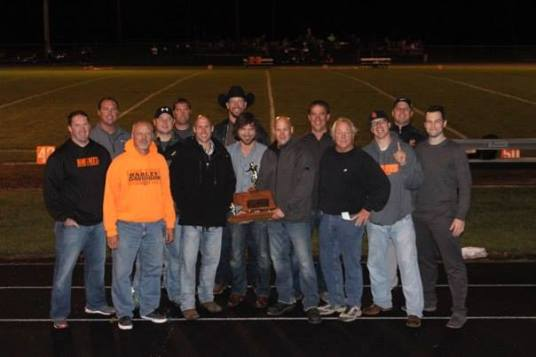 Honored at half-time was the OC championship team from twenty years ago. Pictured from left are: Jim Pelan, Billy Johnson, Coach Dan Engstrom, Kent Puffer, Jason Keogh, Andy Bures Clint Baker, Greg Loftis, Chad Baker, Mark Johnson, Head Coach Clark Benne, Graham Christensen, Andy Rennerfeldt and Christopher Ahrens. Photo Credit/Cheri Droescher.