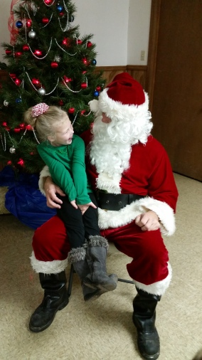 Paisley Peterson is all smiles sitting on Santa's lap. Photo Credit/Brooke Peterson.