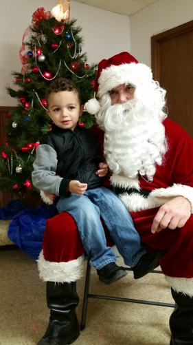 Bowen Perez was happy to see Santa at the Vets Building in Oakland. Photo Credit/Brooke Peterson