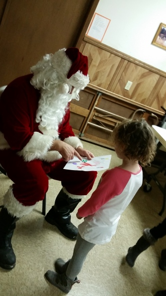 Josie Peterson shows her art work to Santa while he visited the youngsters in Oakland at the Vets Building.
