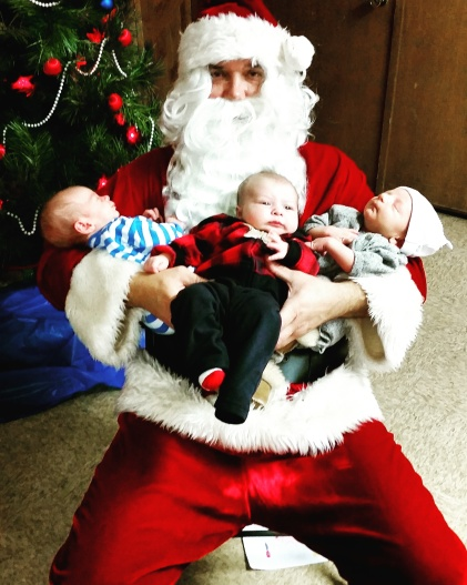 Santa and Emersen Andersen  (6 weeks),  Eli Peterson (7 weeks), Amos Johnson (3 weeks) at the Vets Building in Oakland. Photo Credit/Brooke Peterson.