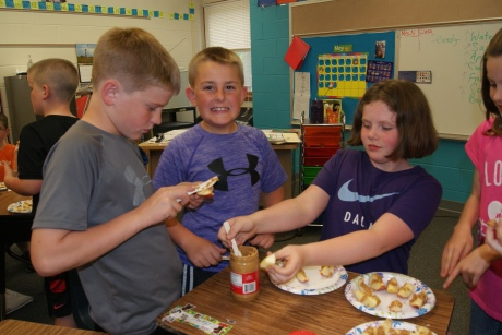 Tekamah third graders get some hands on experience making healthy snacks during the Nebraska Extension Home Alone program last week. Alex Braniff, Cale Belfrage and Eden Roberts work on the tricky job of getting peanut butter to stick to the apple slices snack. Photo Credit/Mary Loftis, Extension Associate.