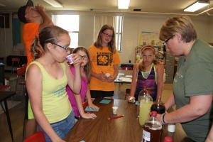 4-H/FFA Livestock Quality Assurance Training included a session on the importance of reading medication labels. This lesson was emphasized by having the participants try to identify what was in the beverage bottles by using the information available on the bottle and tasting and smelling the liquids. These Logan Valley Clovers 4-H members resort to tasting the liquids as the labeling was often incomplete. Hailey Miller of Lyons; Lyndsey Johnson of Oakland, Brent Miller of Lyons (behind); Elise Anderson of Lyons and Avery Bacon of Lyons take turns trying the different beverages as Tess Johnson of Oakland helped serve them. Photo Credit/Mary Loftis.