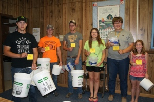 Keeping livestock properly watered takes a lot of water and effort if you are carrying it to your animals as these Burt County 4-H members learned. They are pictured with at least part of the buckets they would have to carry to the animal they were assigned as part of the Livestock Quality Assurance Training last Sunday evening in Oakland. Pictured are: Bailey Fleischman of Tekamah showing part of the 23 gallons of water a 1150 lb. steer would need at 90 degrees; Bryce Uhing of West Point with enough water for a 700 lb steer at 50 degrees; Thomas Hennig of Tekamah with the 6 gallons of water he'd need for a 200 pound hog at 100 degrees; Megan Olson of Tekamah with the much smaller amount she'd need for a 40 lb. lamb at 50 degrees; Blaine Olson of Tekamah with water for his 120 lb. lamb at 80 degrees and Sydney Olsen of Lyons with enough water for a 120 lb. pig at 50 degrees. The rule of thumb in calculating water use is one gallon per 100 lbs. of animal plus more for heat and stress situations.  Photo Credit/Mary Loftis