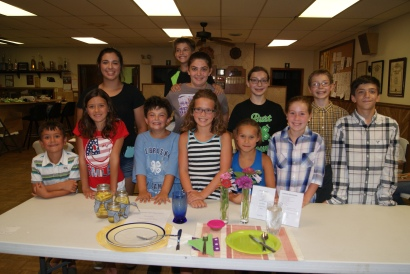 4-H Favorite Foods Contest participants decided on their favorite food, made a nutritious menu and set a table for one in preparation for this contest. Standing behind two pretty tables are: Back row: Ashley Bohannon, Andrew Schlichting, Amelia Schlichting, Faith Roscoe and Paul Roscoe. Front row: Logan Gramke, Ashlynne Gramke, Eli Schlichting, Camryn Brehmer, Karsen Olsen, Sydney Olsen and Caleb Schlichting.  Photo Credit/Mary Loftis