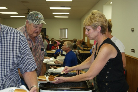 Michelle Smith serves Roger Johnson at the Craig Community fundraiser for the Steve and  Terry Nesemeier family of Craig who lost their home and belongings to a fire earlier this month. Photo Credit/Mary Loftis.