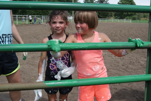 Young 4-H members joined the approximately 100 4-H members, parents, leaders and volunteers on Sunday to help at the Burt County Fairgrounds cleanup day. Here Brylee Ahrens of Oakland and Gracie Klausen of West Point use the glove method to paint the gates and rails on the 4-H Horse Arena.  Photo Credit/Mary Loftis