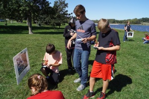 Lyons-Decatur students along with 6th graders from across the county took part in the 6th Grade Conservation Day at Summit Lake last week. Caleb Schlichting, Kaden Frahm, Trevor Cole and Tretyon Frahm roll the dice and record where they as a water molecule will go next from the Cloud in the Water Cycle during one of the Conservation Day activities. – photo by Mary Loftis